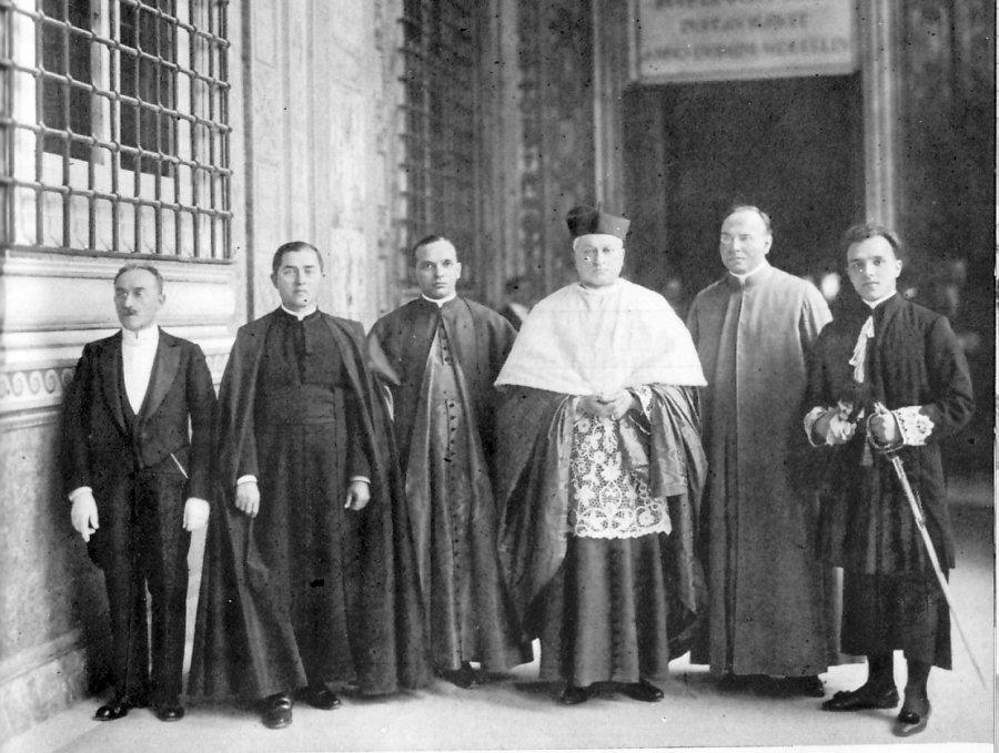 Na zdjęciu ks. August kardynał Hlond w otoczeniu swojej świty w czasie konsystorza. Na lewo od kardynała widzimy jego kaudatariusza (crocia i fioletowa sutanna z czarnymi guzikami), po prawej zaś, ze szpadą, stoi gentiluomo polskiego purpurata.