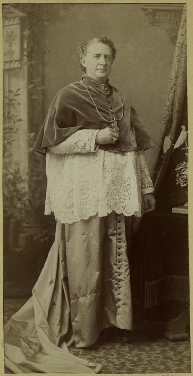 Bp Jan Foley, biskup Detroit, w stroju chórowym z rozpuszczonym trenem sutanny.