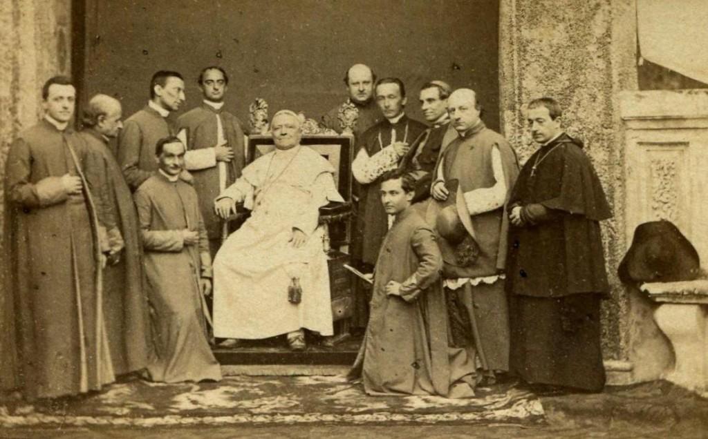 Pius IX w otoczeniu Antykamery Papieskiej (Sekretnej). Mons. Pacca (drugi od prawej) trzyma wspomniany papieski kapelusz. Przy nim stoi Prefekt Kaplicy Apostolskiej, papieski zakrystianin, mons. Martinelli O.S.A. (zakrystianie mieli przywilej noszenia rokiety, ale rzadko jej używali; nosili za to zawsze mantolet i mucet), obok którego leży dawny, trójrożny kapelusz rzymski.